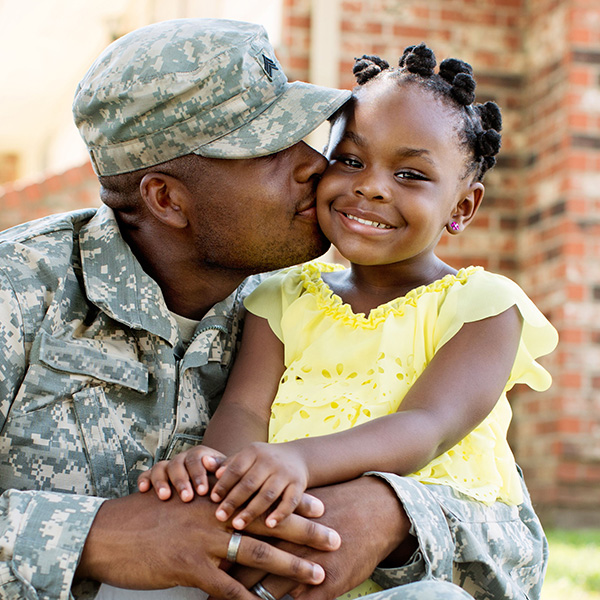 US military man embraces child